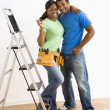 Portrait of couple with ladder. - Stock Photo