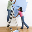 Couple painting wall blue. — Stock Photo #9312378