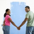 Couple next to half-painted wall. — Stock Photo