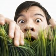 Stock Photo: Surprised mbehind grass.