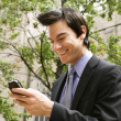 Businessman smiling at cell phone message. — Stock Photo #9312688