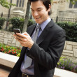 Businessman smiling at cell phone message. — Stock Photo