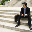 Businessman sitting on steps. - Stock Photo