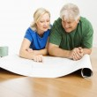 Man and woman looking at blueprints. — Stock Photo