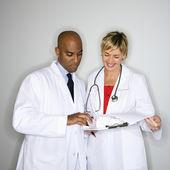 Doctors reading paperwork. — Stock Photo
