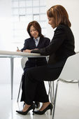 Businesswomen at desk — Stock Photo