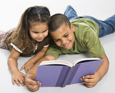 Brother and sister reading book together. — Stock Photo