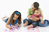 Hispanic girl coloring with brothers. — Stock Photo