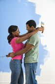 Couple snuggling next to half-painted wall. — Stock Photo