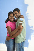 Happy couple next to half-painted wall. — Stock Photo