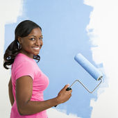 Pretty woman painting wall. — Stock Photo
