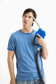 Man holding gas nozzle to head. — Stock Photo