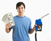 Man with money and gas nozzle. — Stock Photo