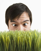 Cross-eyed man behind grass. — Stock Photo