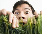 Surprised man behind grass. — Stock Photo
