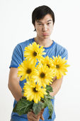 Pouting man holding bouquet. — Stock Photo