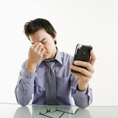Tired businessman with cell phone. — Stock Photo