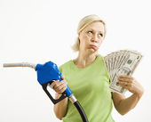 Unhappy woman with gas pump and money. — Stock Photo