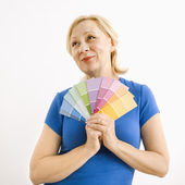 Wishful woman with paint swatches. — Stock Photo