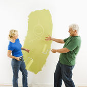 Couple laughing at smiley face painting. — Stock Photo