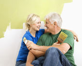 Man and woman snuggling while painting. — Stock Photo