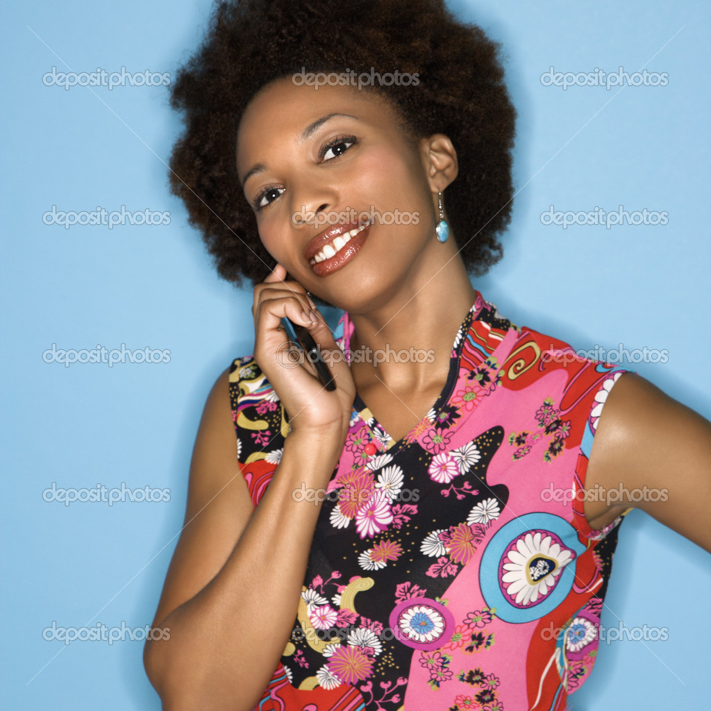 Woman with afro wearing vintage print fabric smiling holding cellphone. — Stock Photo #9310156