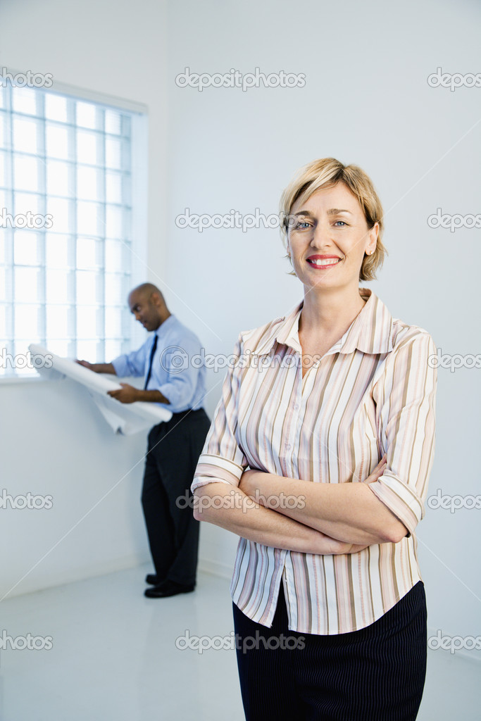 Smiling professional businesswoman standing as man reads architectural plans in background. — Stock Photo #9311112