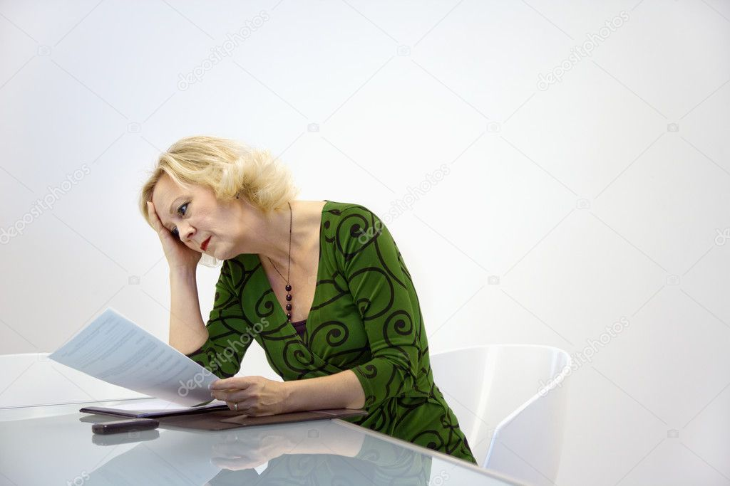Caucasian middle aged businesswoman sitting at office desk reading paperwork. — Stock Photo #9311264