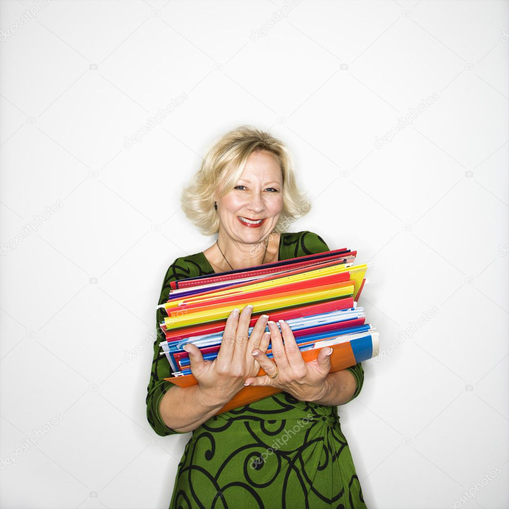 Caucasian middle aged businesswoman carrying stack of folders smiling.  Stock Photo #9311310