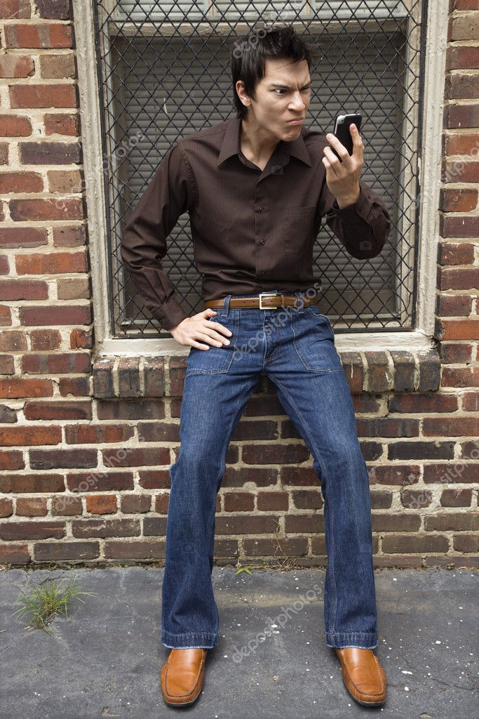 Confused young Asian man next to brick wall and window looking at cell phone. — Stock Photo #9312575