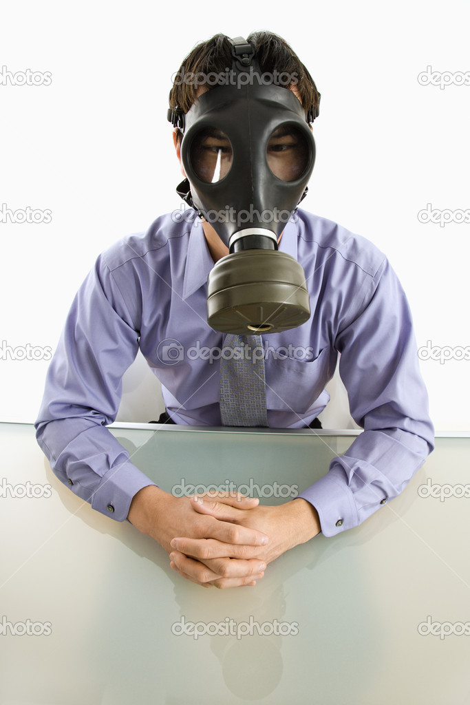 Businessman sitting in white room wearing gas mask. — Stock Photo #9312663