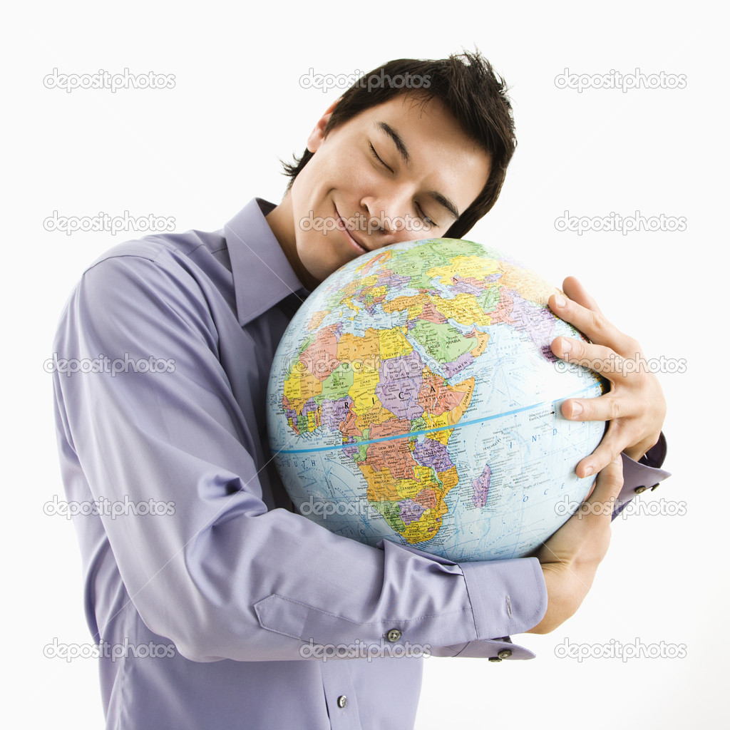 Young Asian man holding globe with happy expression on his face.  Stock Photo #9312730