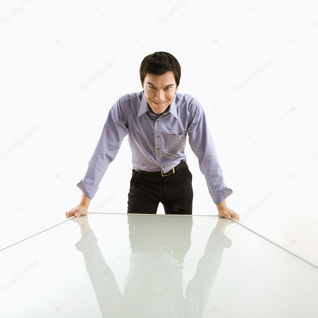 Young Asian business man standing over conference table with devilish grin. — Stock Photo #9312754
