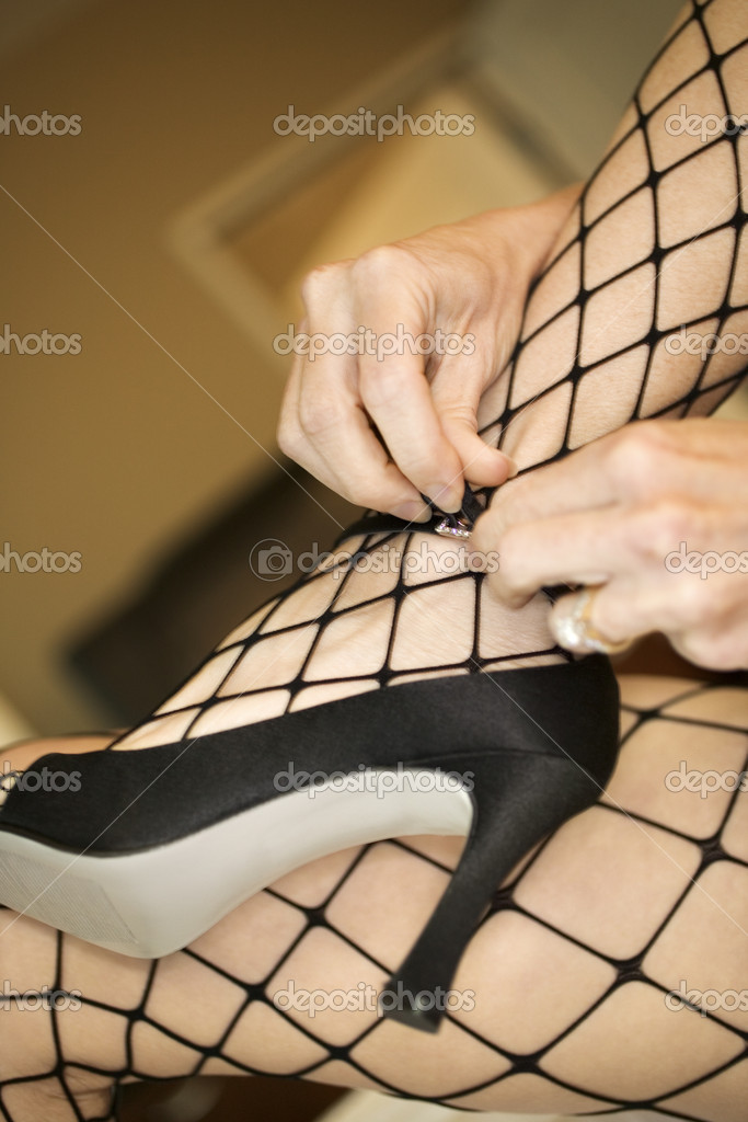 Close up of Caucasian woman in fishnet stockings putting on high heel shoes.  Stock Photo #9313167