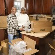Couple unpacking boxes. - Stock Photo