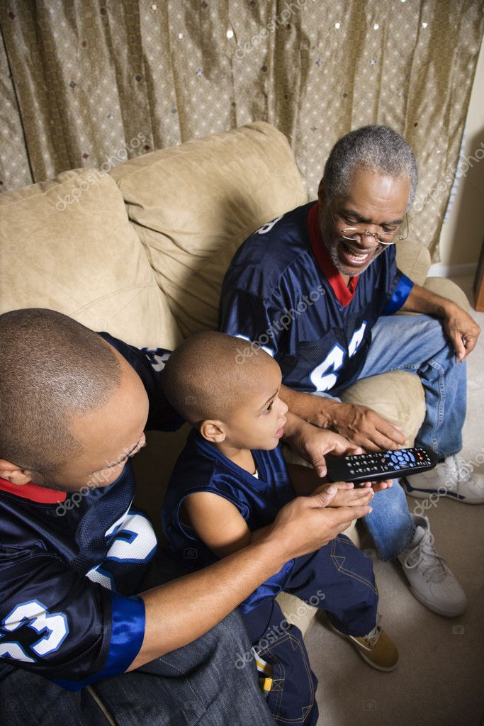 Three male generations of an African-American family watching football game on tv with boy holding remote.  Stock Photo #9329884