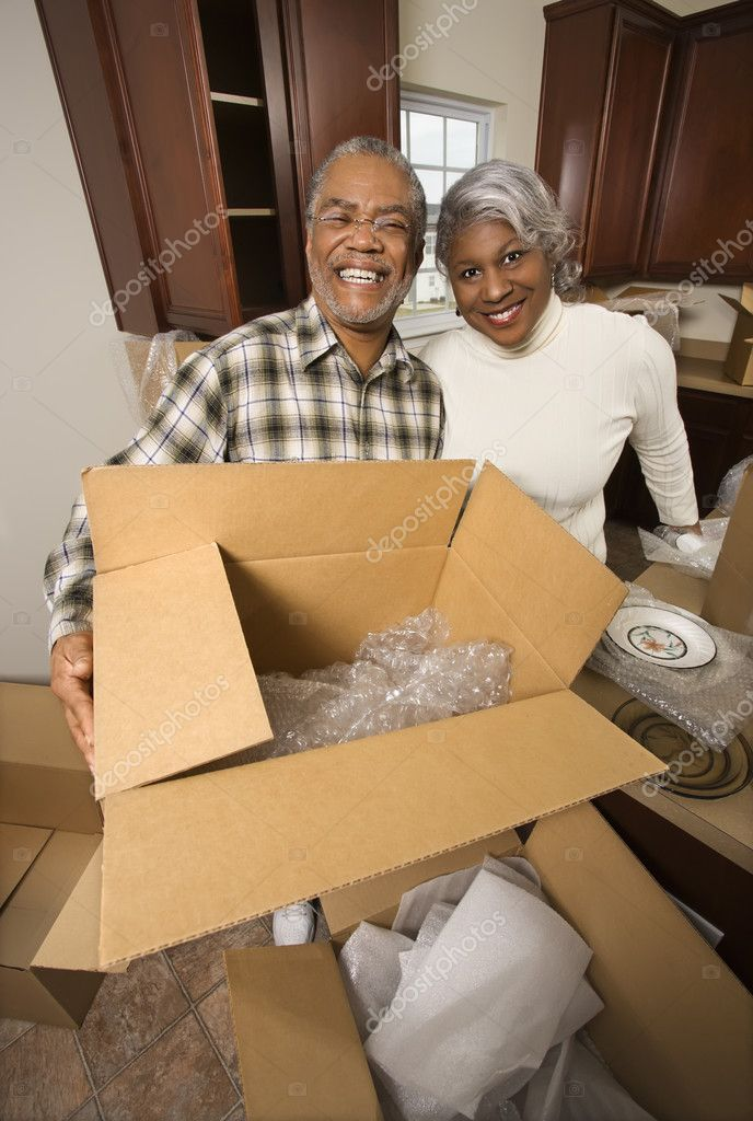 Portrait of middle-aged African-American couple with moving boxes in kitchen. — Zdjęcie stockowe #9329902