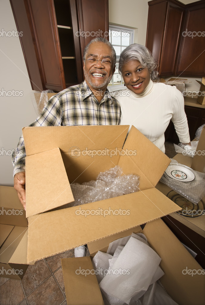 Portrait of middle-aged African-American couple with moving boxes in kitchen. — 图库照片 #9329902