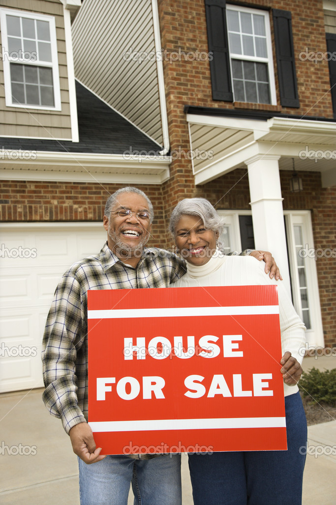 Portrait of middle-aged African-American couple outside house with for sale sign.  Stock Photo #9329910