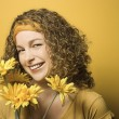 Woman smiling with flowers. — Stock Photo