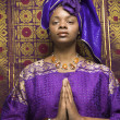 Stock Photo: Young AfricAmericWomPraying and Wearing Traditional AfricDress