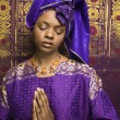 Young African American Woman Praying and Wearing Traditional African Dress — Stock Photo #9330433
