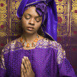 Young African American Woman Praying and Wearing Traditional African Dress - Stock Photo