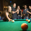 Stock Photo: Young female preparing to hit pool ball.