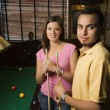 Couple holding poolsticks. — Stock Photo