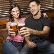 Couple Toasting Their Beers - Stock Photo