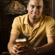 Man at bar smiling. - Stock Photo