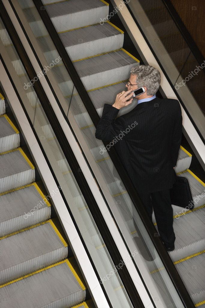 Businessman has a mobile phone conversation while riding the escalator. Vertical shot.  Stock Photo #9330296