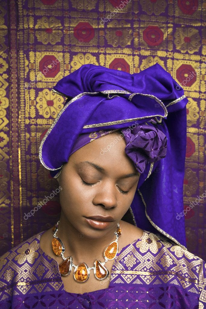Portrait of an African American woman wearing traditional African clothing and closing her eyes in front of a patterned wall. Vertical format. — Stock Photo #9330434