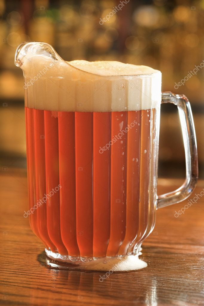Full beer pitcher with foam on a bar counter. Vertical shot. — Stock Photo #9330547